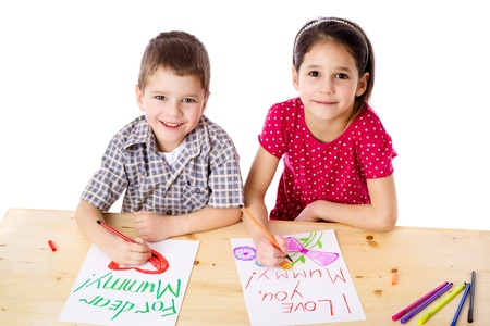 Two smiling kids at the table draw with crayons for mum, isolated on white photo
