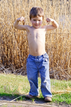 Portrait of a strong kid showing the muscles of his arms, outdoor photo