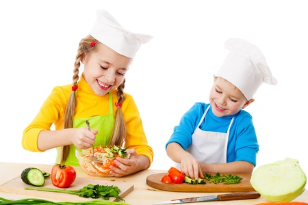 Two smiling kids mixing vegetable salad, isolated on white photo