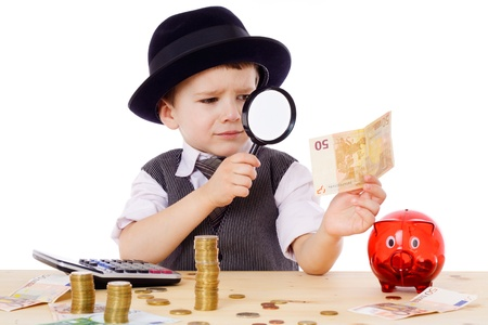counting: Little businessman checks the money with magnifying glass, isolated on white