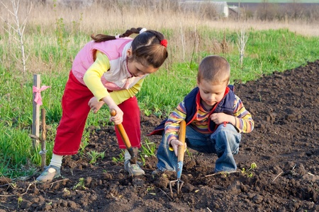 Two little children planting seeds and weed beds in the field