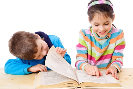 Two kids at the table reading the book together, isolated on white Stock Photo - 13500095