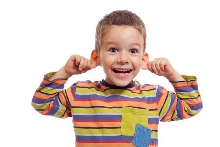 Niño con cara graciosa, se tira de las orejas, aislado en blanco Foto de archivo