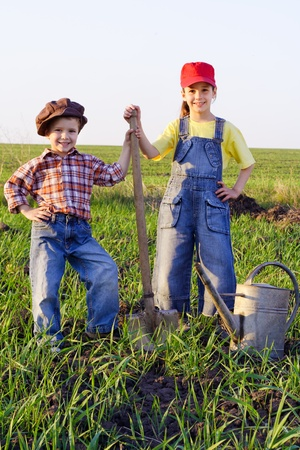Two kids standing in field with shovel and watering can