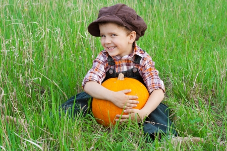 Smiling boy with big yellow pumpkin in hands sitting on the grass photo