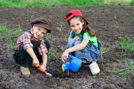 Two kids watering the sprout on field