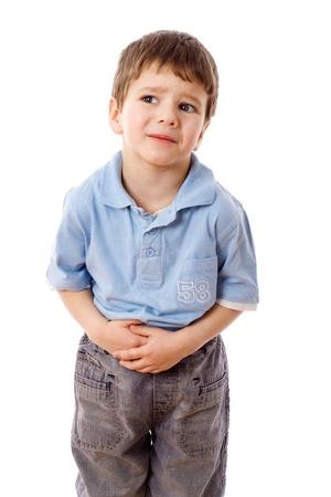dolor de estomago: Niño pequeño que muestra el dolor de estómago, aislado en blanco Foto de archivo