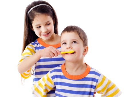 teaches: Girl teaches a boy to brush your teeth, isolated on white
