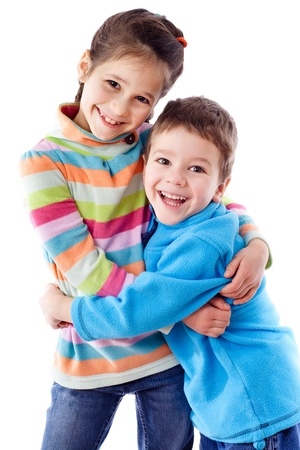 Two happy funny kids standing together and embracing, isolated on white photo