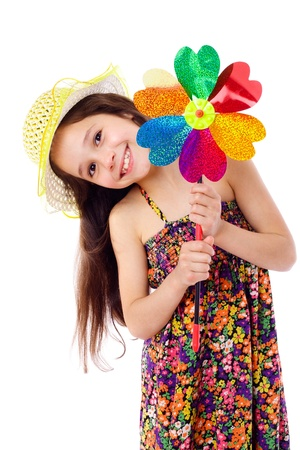 Smiling girl in yellow hat with windmill, isolated on white photo
