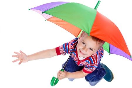 Ragazzino che si siede sotto ombrello colorato, isolato su bianco