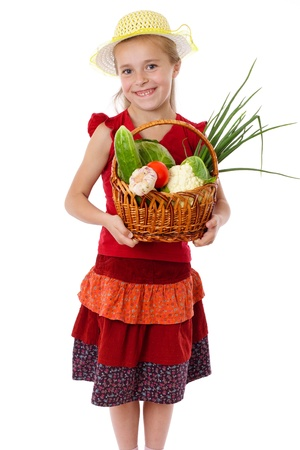 Smiling girl in red dress with basket of vegetables, isolated on white photo