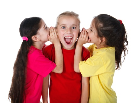 Twee meisjes fluisteren iets aan derde meisje, geïsoleerd op wit