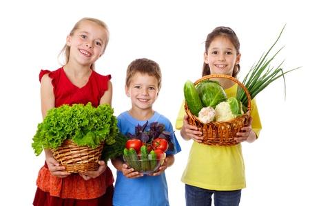 Lachende kinderen met verse groenten in handen, geïsoleerd op wit Stockfoto