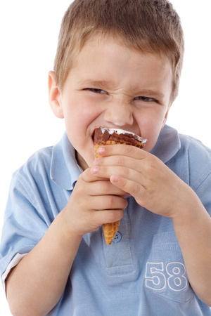 child ice cream: Squinting boy eating the cone of ice cream, isolated on white