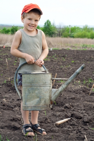 Little boy with old watering can on field Zdjęcie Seryjne