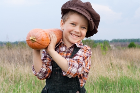 Smiling boy standing with pumpkin on his shoulder in the field photo