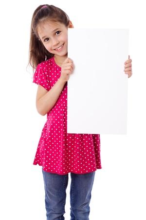 Lachend meisje staan met lege verticale blanco papier in handen, geïsoleerd op wit