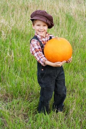 Lachende jongen staat met grote gele pompoen in handen Stockfoto