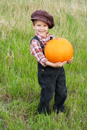 Smiling boy standing with big yellow pumpkin in hands photo