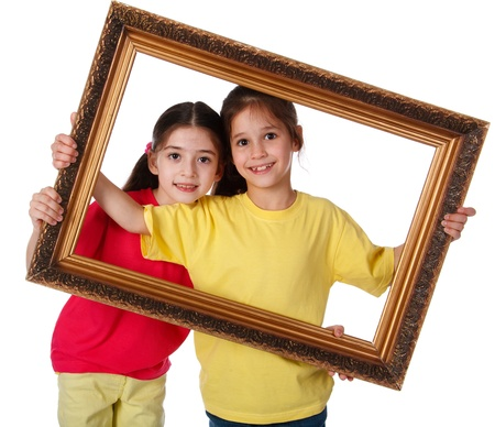 picture person: Two smiling girls looking through a vintage picture frame, isolated on white