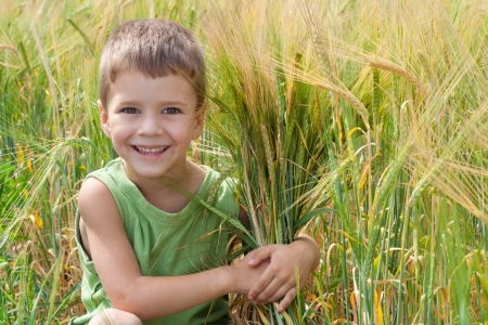 Little boy in a wheat field embracing a spica photo