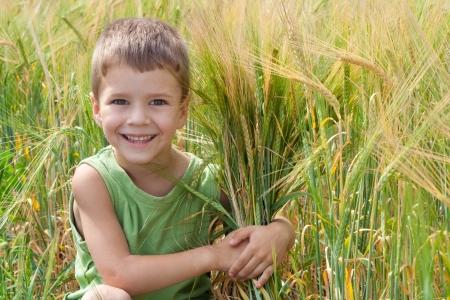 Little boy in un campo di grano che abbraccia una spica