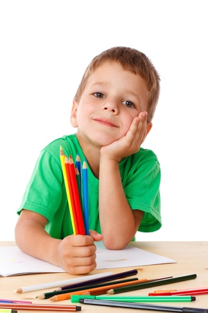 Inspired little boy at the table draw with crayons, isolated on white Stock Photo - 14402368