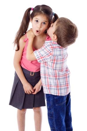 Kleine jongen die iets fluistert aan verrast meisje, geïsoleerd op wit Stockfoto