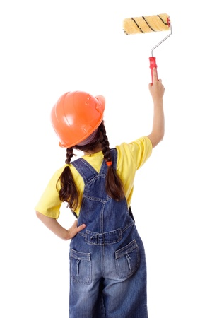 Girl in blue coveralls and hard hat with paintroller on the white wall, rear view, isolated on white photo