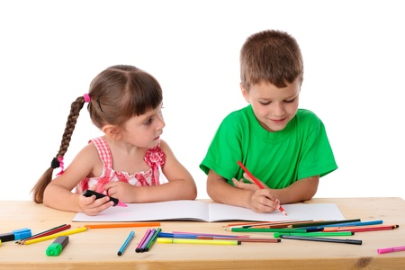 Two little kids at the table draw with crayons, isolated on white Stock Photo - 14412361