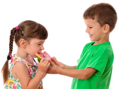 Zwei Kinder essen eine Wassermelone, isoliert auf weiß