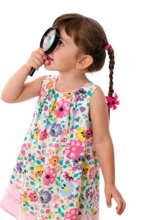 Meisje kijkt door een vergrootglas, geïsoleerd op wit
