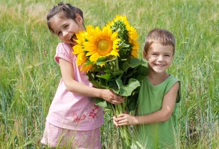 Twee kinderen met bos van zonnebloemen in een tarweveld