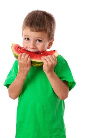 Litle Junge im grünen T-Shirt Essen einer Wassermelone, isoliert auf weiß Standard-Bild