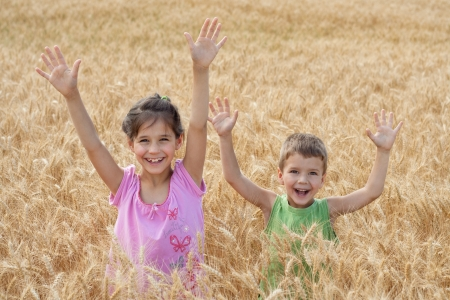 Two kids on a wheat field with raised up hands photo
