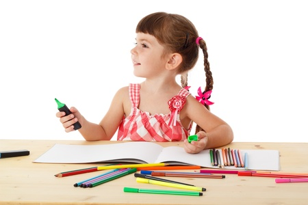 Inspired little girl at the table draw with crayons, isolated on white Stock Photo - 14634373