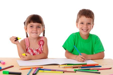 Dos pequeños niños sonrientes en el sorteo mesa con lápices de colores, aislados en blanco Foto de archivo