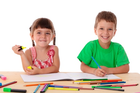 little table: Two smiling little kids at the table draw with crayons, isolated on white Stock Photo