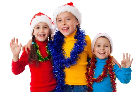 Three happy children in Santa hats with greeting sign, isolated on white photo