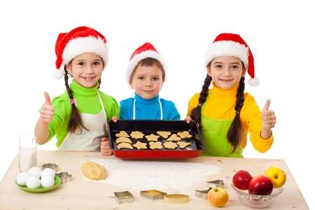 Three smiling kids with Christmas cooking and thumbs up sign, isolated on white photo