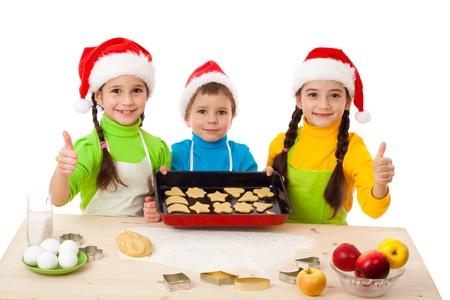 Tre bambini sorridenti con la cottura di Natale e pollice in alto segno, isolato su bianco