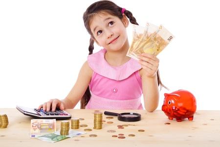 Dreaming meisje aan de tafel telt geld, geïsoleerd op wit Stockfoto