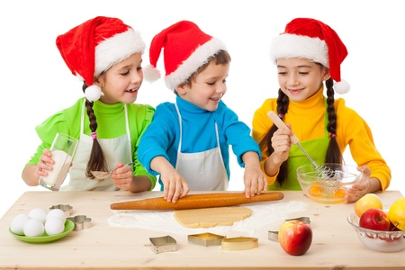 little dough: Three smiling kids with Christmas cooking, isolated on white