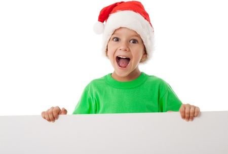 Screaming little boy with Christmas hat standing with empty blank in hands, isolated on white photo