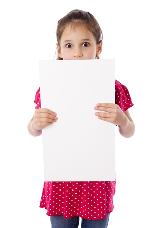 child holding sign: Surprised girl standing with empty vertical blank paper in hands, isolated on white