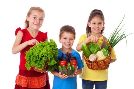 Lachende kinderen met verse groenten in de mand, geïsoleerd op wit