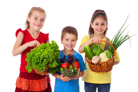 Smiling kids with fresh vegetables in basket, isolated on white Stock Photo