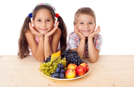 Happy kids sitting on the table with plate of fruit, isolated on white Stock Photo