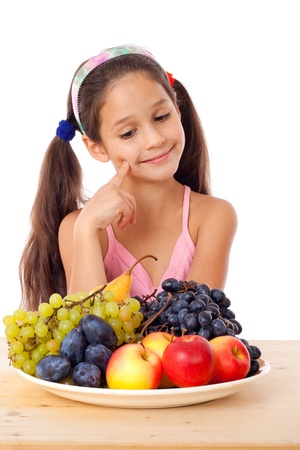 Girl sitting on the table with plate of fruit, isolated on white photo